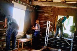 Installation av väggvärmerör på timmervägg som sedan putsas med lera.